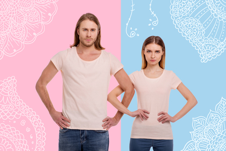 Confident young light haired couple keeping hands on waist and arm in arm while looking at you and expressing seriousness against blue and pink background with white pattern