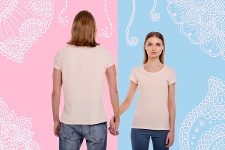 Waist up of pretty long haired girl standing in front of you and taking her boyfriend by hand while her boyfriend standing back against pink background