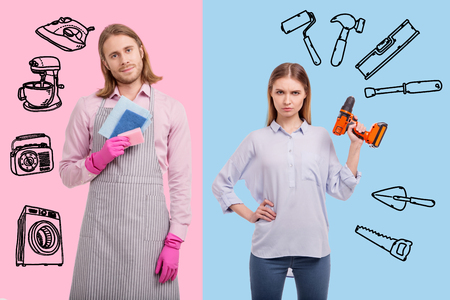 Interesting couple. Young woman standing for a gender equality and holding a drill while her husband washing the dishes