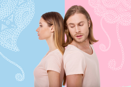 Close people. Young curious sensitive man turning his head and trying to looking at his calm wife while standing back to back with her during their psychological exercise Stock Photo