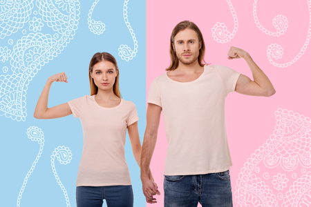 Strong people. Enthusiastic sporty couple holding hands and showing their strength while standing against the colorful background