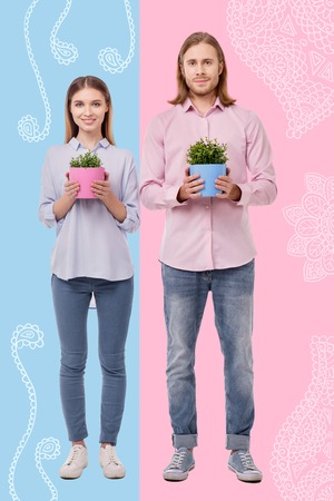 Cheerful gardeners. Positive professional gardeners smiling and standing with lovely flower pots in their hands while being at work