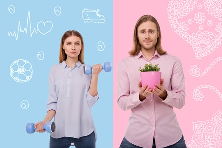 Different timespending. Cheerful active woman holding hand weights and her emotional husband standing with a flower pot 写真素材