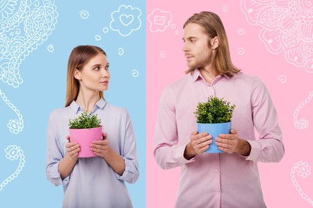 Loving plants. Romantic young couple looking at each other while being in their flower shop and holding colorful flower pots