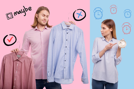 Late for work. Relaxed young man choosing a shirt and being late for work while his emotional worried wife pointing to the clock Stock Photo - 101768426