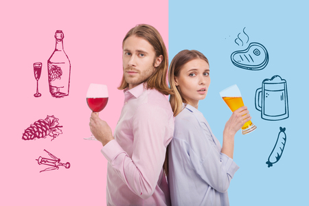 Delicious drinks. Young relaxed couple feeling good while standing back to back and drinking beer and wine Stock Photo