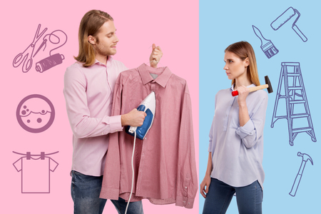 Ironing clothes. Strong serious woman standing with a hammer while her kind calm husband ironing his shirt