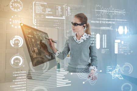 Clever woman. Experienced database administrator carefully touching the screen with a stylus while working in virtual reality glasses Banque d'images