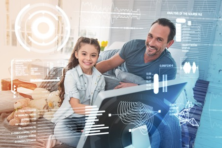Looking happy. Cheerful emotional girl sitting in front of a modern device and her kind father smiling while being near