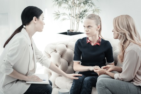 Dont touch me. Depressed unconfident serious girl sitting on the sofa with her mother holding her hands and looking at a woman. Stock Photo