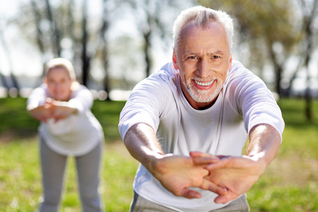 Full of energy. Joyful aged man being in a great mood while doing physical exercises