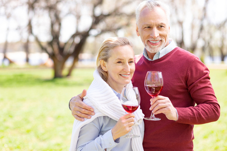 Wonderful drink. Positive aged couple looking at you while holding glasses with wine