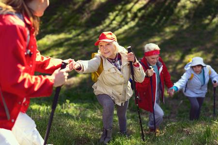 Gran día. Mujer de edad inspirada dando una mano y senderismo con sus amigos Foto de archivo