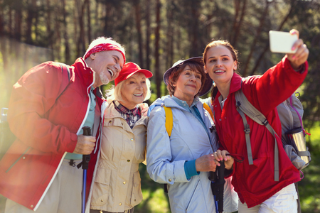 Say cheese. Inspired aged people taking pictures while hiking with their guide Stock Photo
