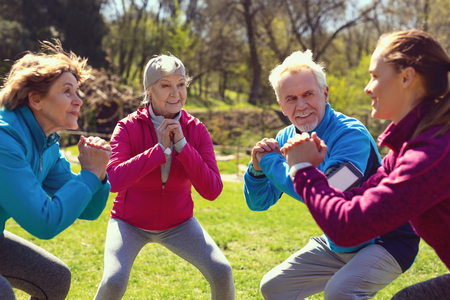 Great training. Content aged woman smiling and exercising with her friends in the park