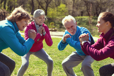 Staying healthy. Cheerful aged woman smiling and exercising with her friends in the park