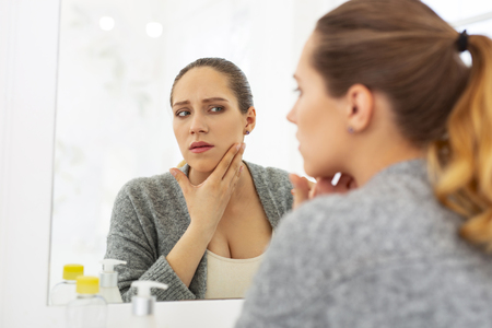 Common problem. Uneasy worried woman looking at mirror and putting hand on neck Stock Photo - 101992232