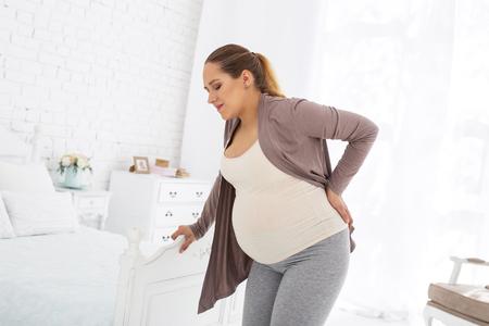 Ongemak tijdens de zwangerschap. Boze zwangere vrouw die en haar rug blijft aanraken