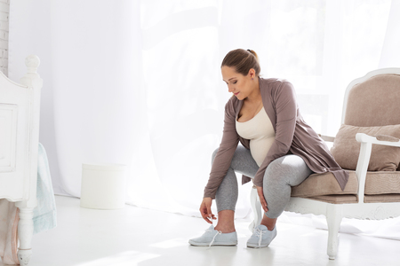 Total concentration. Pleasant pregnant woman lacing shoes while sitting on chair