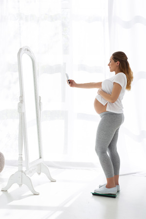 Daily selfie. Glad pregnant woman using phone and standing in profile Foto de archivo