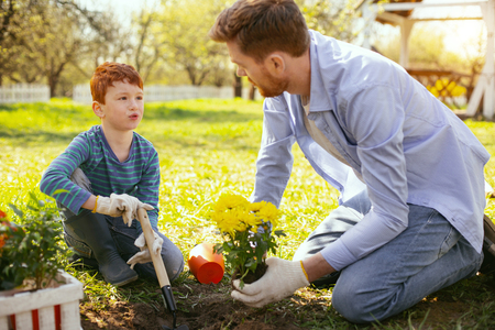 Environmental lesson. Nice pleasant man looking at this sin while teaching his to plant flowers Stok Fotoğraf
