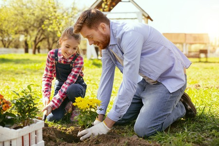 Funny activity. Joyful positive father and daughter having fun while planting flowers together