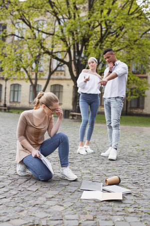 Insulting students. Two insulting students abusing their fellow student dropping her things on the ground Stock Photo