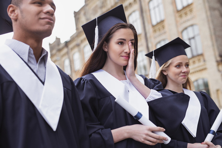 Feeling touchy. Dark-haired beautiful student feeling very touchy while standing near university on her graduation day Stock Photo
