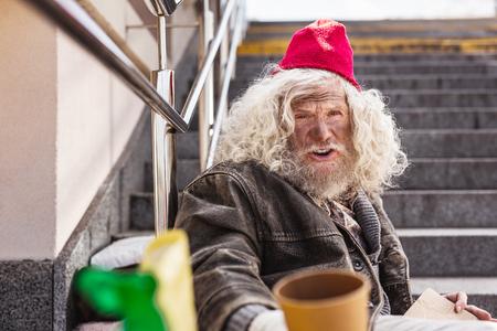 Street beggar. Cheerless homeless man sitting on the street while asking for money