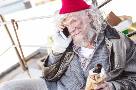 Mobile connection. Positive nice man making a phone call while holding a bottle of beer Stock Photo