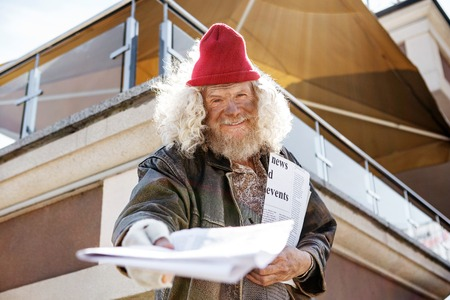 For you. Positive cheerful man looking at you while giving you a newspaper
