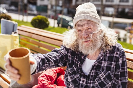 Life challenge. Poor bearded man holding a plastic cup while being in the need for money