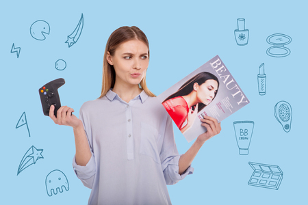 Difficult choice. Young beautiful woman standing with a game console and a fashion magazine while choosing the best activity for herself