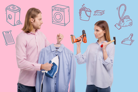 Ironing clothes. Serious young woman standing with a drill and a hammer while her calm husband ironing the shirt