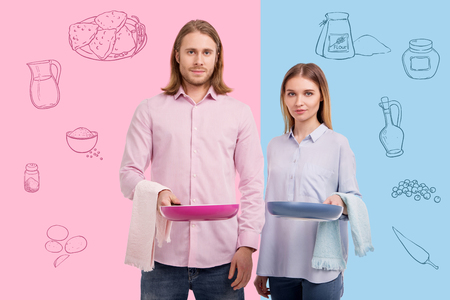 Standing with frying pans. Relaxed young couple standing with colorful frying pans and towels while being in their kitchen and working together