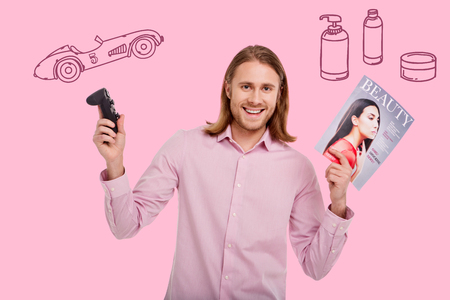 Happy man. Cheerful handsome longhaired man feeling impressed while holding a modern game console and a fashion magazine