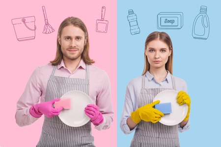 Holding plates. Young long haired man looking calm while standing with his serious wife and washing plates with her