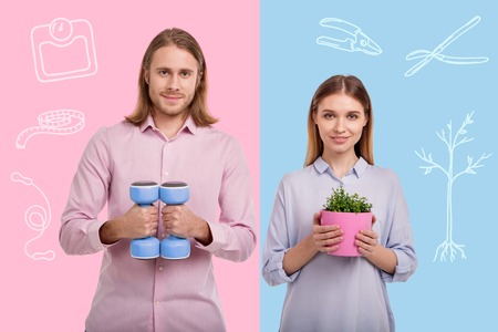 Satisfied with hobbies. Positive adorable loving couple looking satisfied with their new hobbies while standing with hand weights and a flower pot Reklamní fotografie