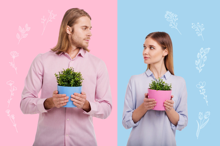 Common hobby. Calm couple wearing similar casual clothes and looking at each other while standing with flower pots Stock Photo