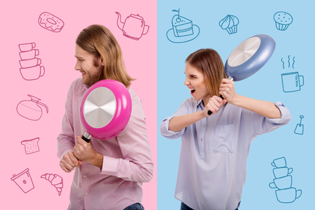 Kitchen fight. Furious young housewife screaming and carrying a heavy frying pan while threatening her husband with it 写真素材