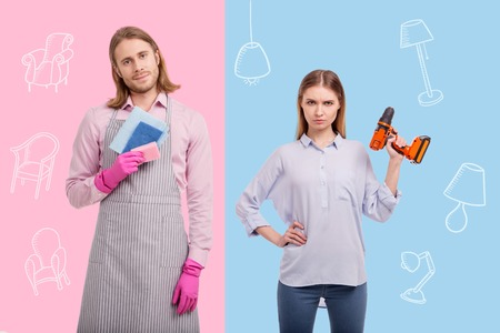 Gender equality. Peaceful young man wearing an apron and holding colorful sponges while his serious strong wife looking confident with a drill in her hands