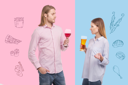 Disgusting drink. Expressive young woman holding a glass of beer and frowning while her calm husband feeling satisfied with his tasty wine
