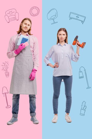 Strange family. Strong young woman holding a big heavy drill and her smiling husband wearing an apron while washing the dishes