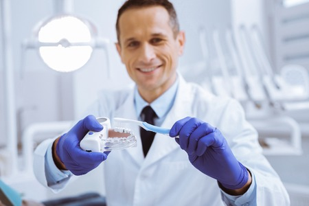 Useful activity. Cheerful medical worker holding artificial teeth while cleaning it 스톡 콘텐츠