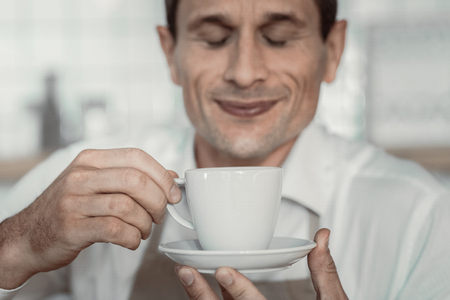Having break. Portrait of delighted barista that closing eyes and going to drink coffee