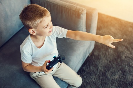 Curious. Attentive cheerful little boy pointing at the screen while holding a games console in his right hand