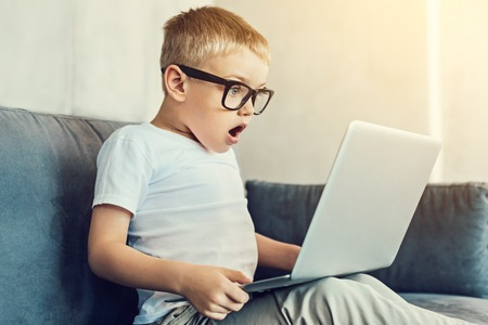 Surprising moment. Extremely surprised child in big glasses looking at the screen of his new laptop