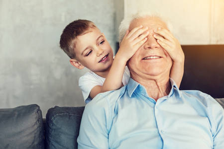 Guess who. Friendly little playful child closing the eyes of a senior man with his hands