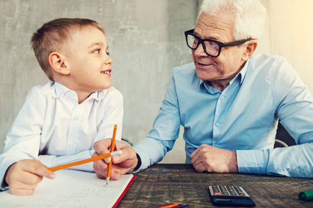 Clever grandfather. Happy smiling boy doing homework together with his helpful grandfather Stockfoto