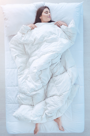 Comfortable sleep. Top view on a joyful brunette covered in a duvet falling asleep in a starfish position in bed. Standard-Bild